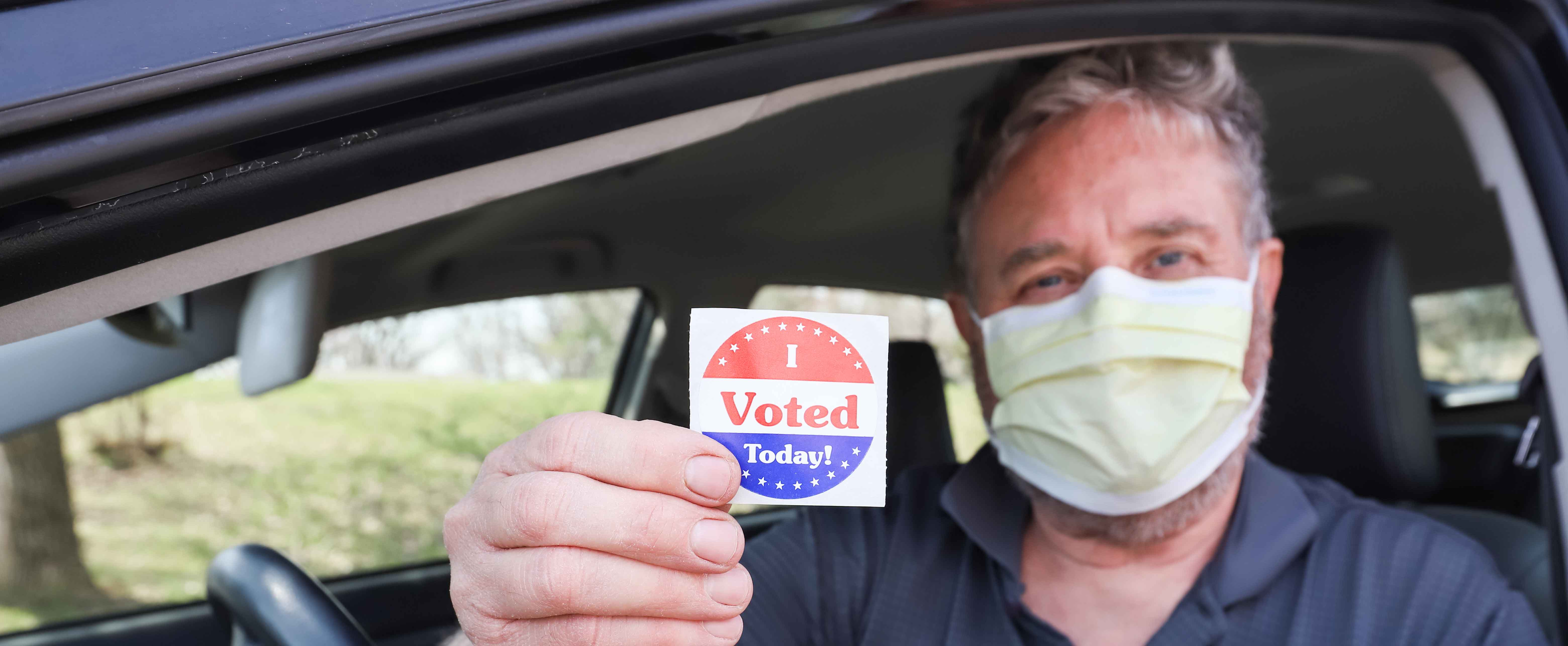 """A man wearing a surgical mask holds out a sticker that says """"I VOTED"""""""