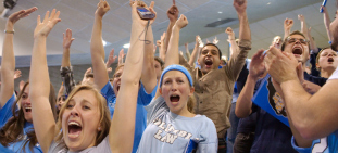 A photo of students cheering wildly at a basketball game.