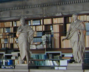 Photo of two statues and stacks of law books