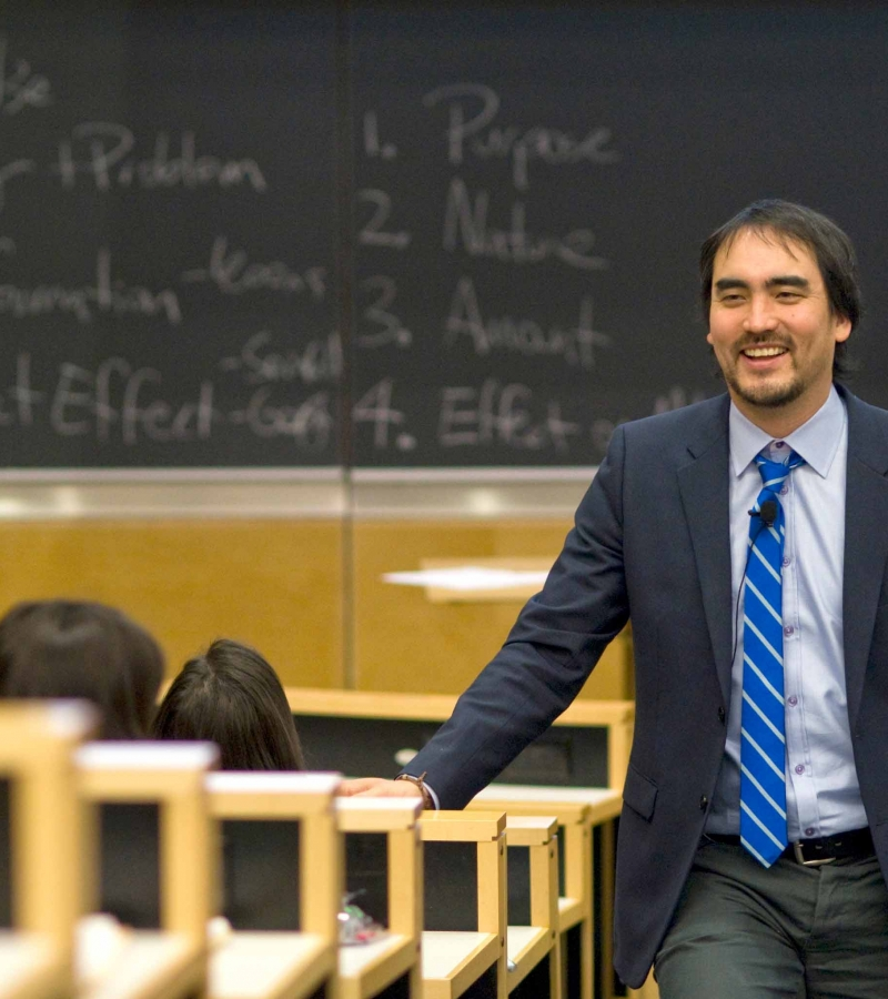 Professor Tim Wu walks up the aisle of a lecture hall.